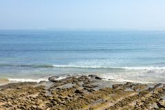 Rotsachtig strand met achtergrondmist Stock Foto