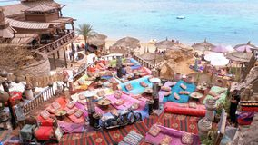 Rotsachtig strand met Arabische koffie in retro stijl op de rode overzeese kust met paraplu's, zonbedden en koralen Egypte stock videobeelden