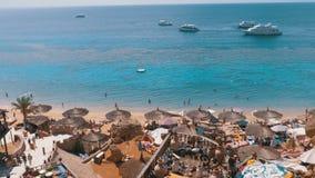 Rotsachtig strand met Arabische koffie in retro stijl op de rode overzeese kust met paraplu's, zonbedden en koralen Egypte stock video