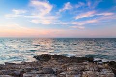 Rotsachtig strand met de mooie achtergrond van de zonsonderganghemel Royalty-vrije Stock Foto's