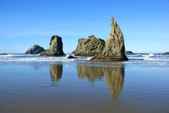 Rotsachtig strand met keien die tegen het zand en het water nadenken Stock Foto