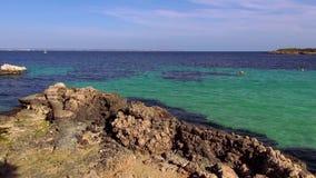 Rotsachtig strand met turkoois blauw water van de oceaan stock footage