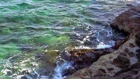 Rotsachtig strand met turquois blauw water van de oceaan stock videobeelden
