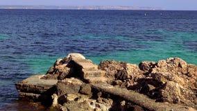 Rotsachtig strand met turquois blauw water van de oceaan stock video
