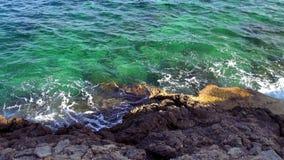 Rotsachtig strand met turquois blauw water van de oceaan stock footage