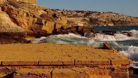 Rotsachtig strand met wild water en brekende oceaangolven stock videobeelden