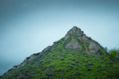 Rotsachtige bergbovenkant met gras en mist royalty-vrije stock foto