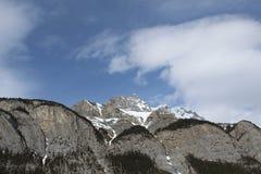Rotsachtige bergen en bomen met blauwe hemel en wolkenclose-up Stock Foto