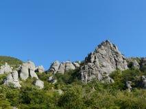 Rotsachtige bergen op een blauwe hemel als achtergrond Royalty-vrije Stock Afbeeldingen