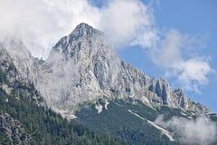 Rotsachtige die helling van een berg gedeeltelijk door mist in de Tennen-waaier in de Oostenrijkse Alpen dichtbij de stad van Wer stock afbeelding