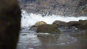 Rotsachtige die kust door de golven wordt gewassen stock video