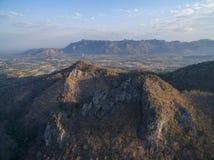 Rotsachtige klip en bergketen met hoogland en huizenachtergrond Stock Afbeelding