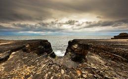 Rotsachtige klippen door oceaan Royalty-vrije Stock Afbeelding