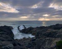 Rotsachtige kosten met zonsondergang tussen de wolken stock foto's