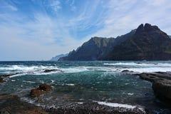Rotsachtige kust, blauwe hemel, golven en bergen royalty-vrije stock afbeeldingen
