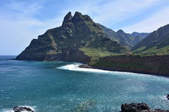 Rotsachtige kust, blauwe hemel, golven en bergen stock foto's