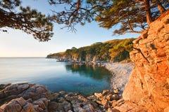 Rotsachtige kust in de stralen van de het plaatsen zon Royalty-vrije Stock Afbeelding