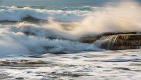 Rotsachtige kust met golvende oceaan en windgolven die op ro verpletteren Stock Fotografie