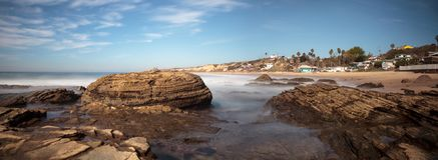 Rotsachtige kust met Strandplattelandshuisjes die Crystal Cove State Park B voeren Stock Foto's