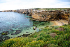 Rotsachtige kust met zandstrand stock foto's