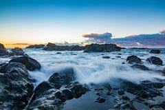 Rotsachtige kust over de oceaan tijdens zonsondergang stock afbeelding