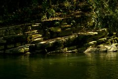 Rotsachtige kust van een bergstroom in het regenwoud stock fotografie