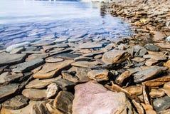 Rotsachtige kust van het meer Stock Afbeeldingen