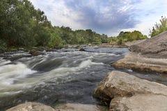 Rotsachtige kusten, stroomversnelling, snelle rivierstroom, heldergroene vegetatie en een bewolkte blauwe hemel in de zomer Stock Afbeelding
