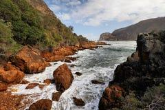 Rotsachtige kustlijn dichtbij de Knysna-Hoofden, Zuid-Afrika Royalty-vrije Stock Foto