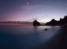 Rotsachtige kustlijn na zonsondergang Stock Foto