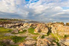 Rotsachtige kustlijn op de oceaan in DE Kelders, Zuid-Afrika, beroemd voor walvis het letten op Wintertijd, bewolkte en dramatisc stock afbeeldingen