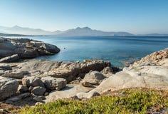 Rotsachtige kustlijn van Corsica met citadel van Calvi in de afstand royalty-vrije stock afbeeldingen
