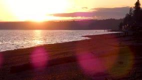 Rotsachtige oever bij schemer onder heldere zonsondergang stock videobeelden