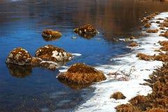 Rotsachtige oever met ijs Stock Fotografie
