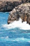 Rotsachtige overzeese klip, tegen het overzees op een zonnige dag Stock Foto's