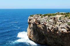 Rotsachtige overzeese klip, tegen het overzees op een zonnige dag Stock Afbeeldingen
