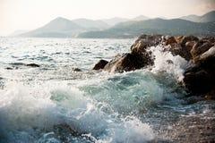 Rotsachtige overzeese kust en golven het bespatten Stock Foto