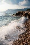 Rotsachtige overzeese kust en golven het bespatten Stock Afbeelding