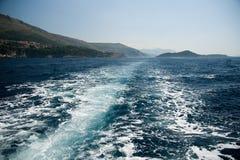 Rotsachtige overzeese kust en golven het bespatten Stock Afbeeldingen