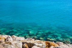Rotsachtige overzeese kust en turkoois water op een duidelijke dag stock afbeelding