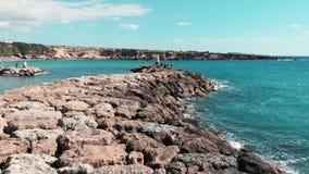 Rotsachtige overzeese pijler met oceaangolven die klippen raken die tot het witte schuim en water bespatten leiden Satellietbeeld stock videobeelden