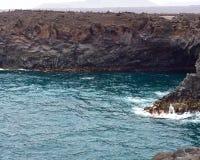 Rotsachtige steile kust van vulkanisch eiland van bevroren lava en azuurblauwe uitgestrektheid van oceaan openlucht stock foto's