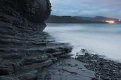 Rotsachtige strandkust in een stormachtige zonsondergang Stock Afbeelding