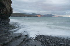 Rotsachtige strandkust in een stormachtige zonsondergang Stock Foto