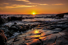 Rotsachtige strandzonsondergang Stock Afbeelding