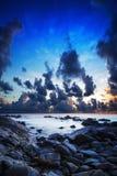 Rotsachtige zeekust bij schemer Stock Fotografie