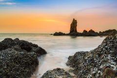Rotsachtige zeekust lange blootstelling met dramatische hemel royalty-vrije stock fotografie