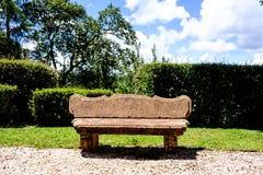 Rotsbank in mooi park met groene haag en grintweg Stock Foto