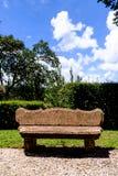Rotsbank in mooi park met groene haag en grintweg Stock Afbeelding
