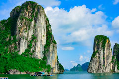 Rotseilanden die dichtbij dorp in Halong-Baai drijven stock fotografie